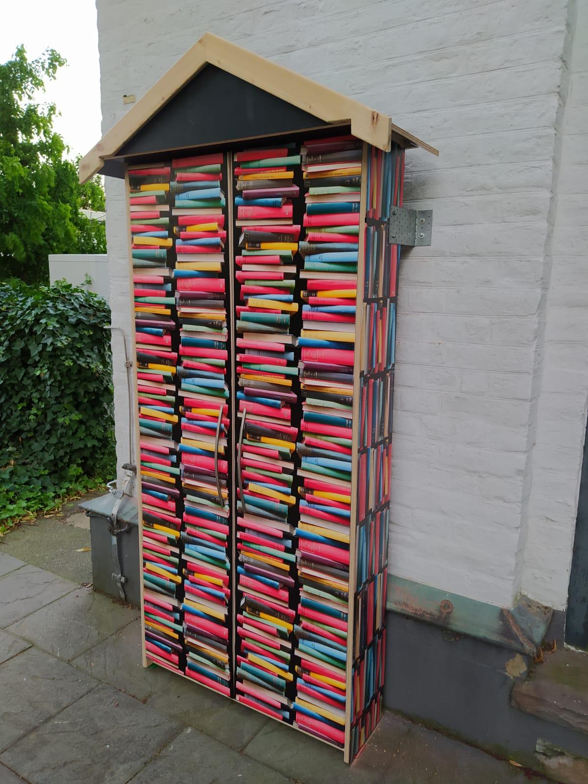 Bücherschrank an der Kirchenwand. Beklebt mit einer Folie mit bunten Büchern