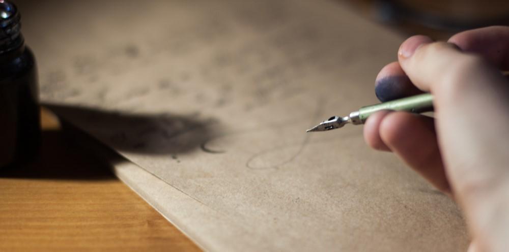 Eine Hand mit tintenbeschmierten Zeigefinger hält eine Tuschefeder über einen handgeschriebenen Brief