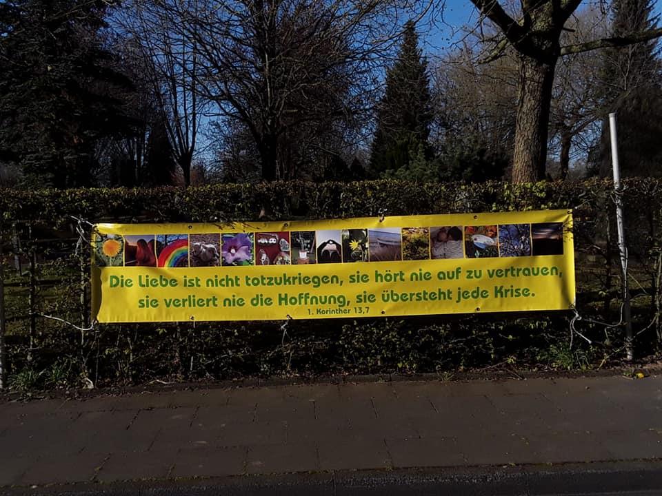 Banner an unserer Friedhofshecke gegenüber der Kirche mit verschiedenen Bildern und Vers aus 1. Korinter 13,7 - Die Liebe ist nie totzukriegen, sie hört nie auf zu vertrauen, sie verliert nie die Hoffnung, sie übersteht jede Krise