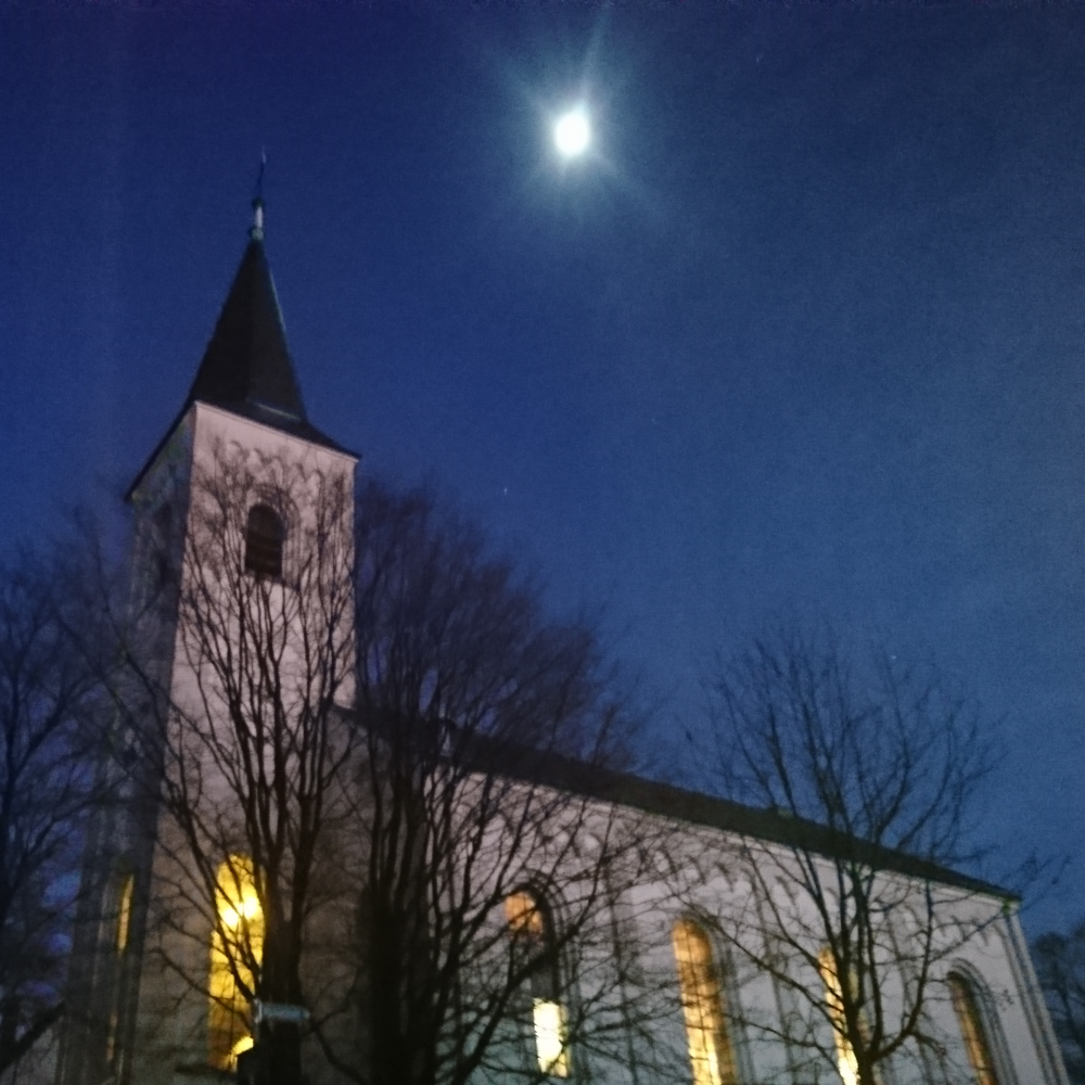 Widderter Kirche am Abend mit erleuchteten Fenstern, darüber der Vollmond