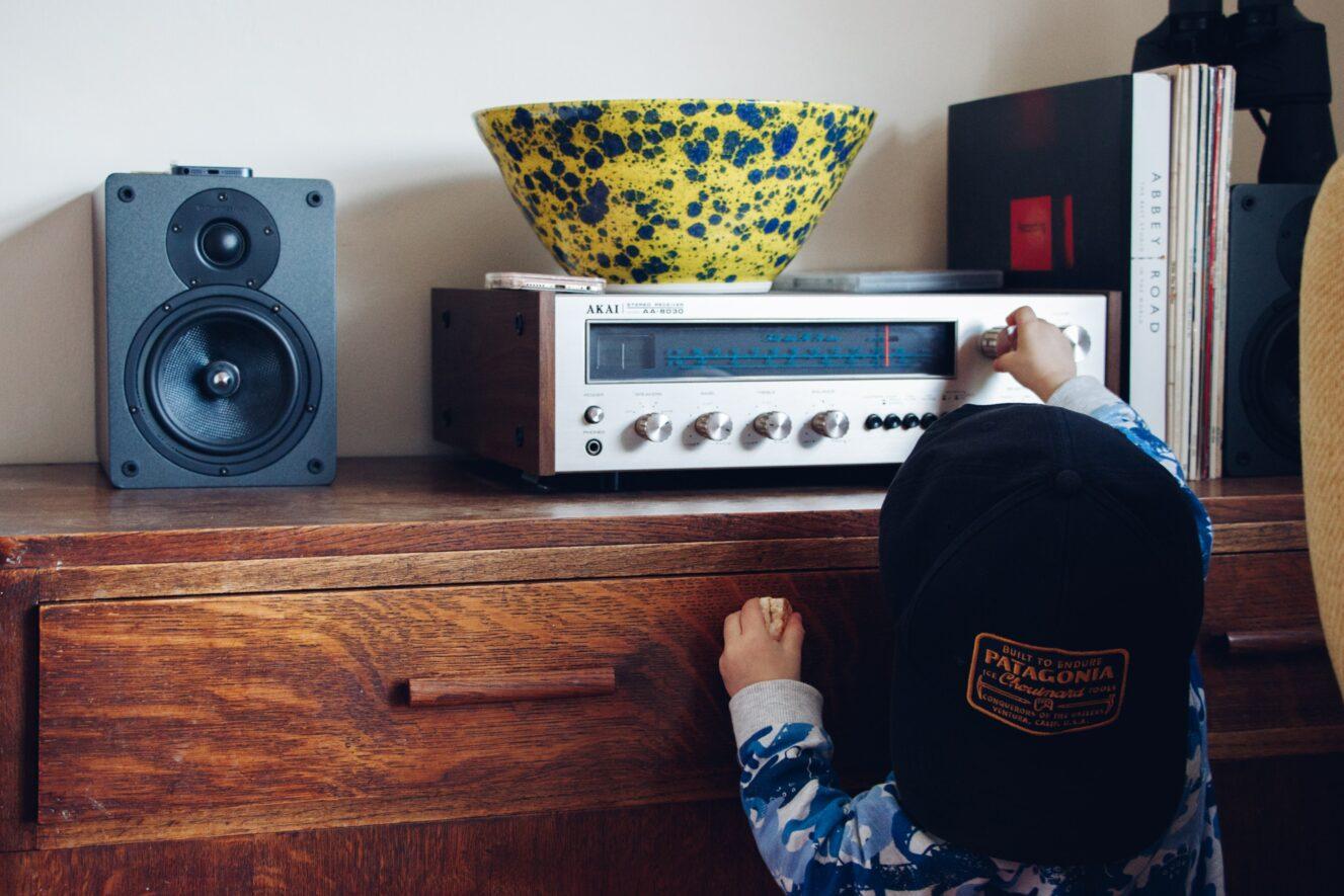 kleiner Junge dreht am Senderknopf eines Radios auf einer Komode